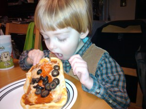 Jedrek taking a big bite of pepperoni and black olive pan pizza